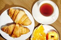 Backround kontinental frukost med guld- franska giffel, frukter och kopp te på trätabellen Stort val på morgon smakligt Royaltyfria Bilder