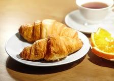 Backround kontinental frukost med guld- franska giffel, frukter och kopp te på trätabellen Stort val på morgon smakligt Arkivbilder