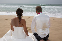 Backs of bride and groom against the ocean looking away royalty free stock photography