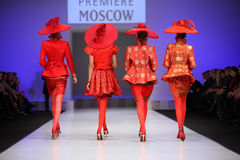 Backs of four women walk the catwalk. MOSCOW - FEBRUARY 22: Backs of four women wear red suits from Slava Zaytzev walk the catwalk in the Collection Premiere stock photos
