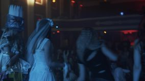 Backs of girls in halloween costumes dancing on scene at night club party. In front of people stock footage