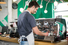 With backs male barista making coffee. And serving coffee royalty free stock photo