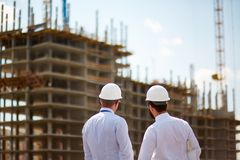 Backs of modern architects. Male architects in helmets and formalwear standing in front of new construction stock photography