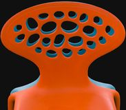 Backs of orange and blue plastic chairs. Before black background stock image