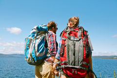 Backs of travelers. Two hikers with backpacks spending leisure or vacation by the seaside royalty free stock image