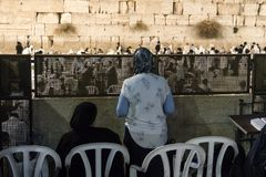 Backs of two Jewish women in women's section watching men praying at Western Wall, Judaism s holiest prayer site in the Old City. Of Jerusalem. Dividing men and stock photos