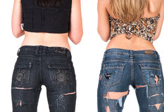 Backs of two young women. Backs and rears of two young women wearing casual tops and jeans with holes.  White background Stock Photography