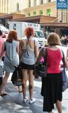 Backs of women shoppers with all their bags waiting for the crosswalk in near Anzac Square. 2-4-2015 Brisbane Australia - Backs of women shoppers with all their stock image