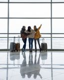 Three girls with bags staring at runway royalty free stock photography