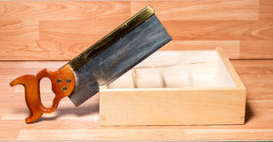Backsaw cuts into a wooden box Royalty Free Stock Photography