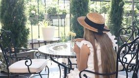 Backshot de la pequeña muchacha bonita en el sombrero de paja que se sienta en un café de la calle que bebe el chocolate caliente metrajes