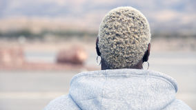 Backside of an african blond woman. With a hoody stock image