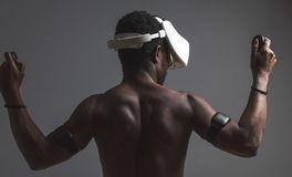 Backside of African male muscular athlet with naked torso using vr headset royalty free stock photos