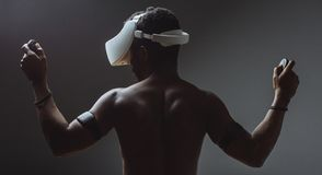 Backside of African male muscular athlet with naked torso using vr headset royalty free stock photography
