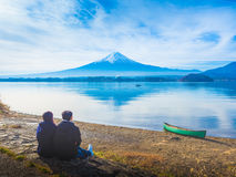 Backside of asia couple traveler 30s to 40s sit and see lake at royalty free stock photos