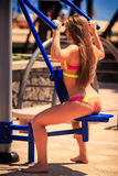 Backside blonde girl in bikini sits on weight stack simulator Royalty Free Stock Image