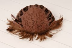 Backside of brown wig, inside, the internal side of wig, curly h. Air is on white table Stock Photo