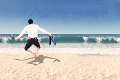 Backside of businessman jumping on beach Royalty Free Stock Images