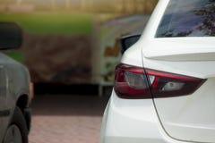 Backside car stop in parking lot. ฺBackside of white car stop in parking lot Royalty Free Stock Images