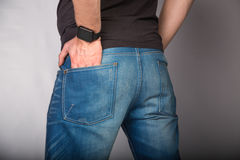 Backside Cose Up Of A Young Fashion Man In Jeans With Hand In Pocket  On Gray Background