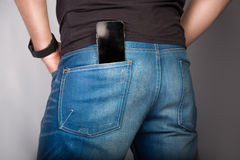 Backside cose up of a young fashion man in jeans with phone in pocket on gray background. Backside of a young fashion man in jeans with phone in pocket on gray royalty free stock photography