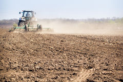 backside cultivator raises great dust on ploughed soil Royalty Free Stock Photos