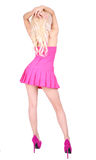 Backside of dancing blonde woman. In short pink dress and high heels on her legs isolated on white royalty free stock photography