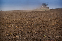 Backside distant cultivator raises great dust on ploughed soil. Backside view distant tractor cultivator on big wheels raises great dust on ploughed ground on royalty free stock image