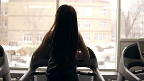 Backside footage in slow motion of a sportive girl with long brunette hair running on a treadmill. Indoors. Backside footage in slow motion of a sportive girl stock footage