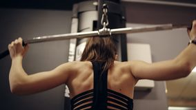 Backside footage of sportive strong brunette female workouter in striped black sports bra pulling the bar of lat. Pulldown mashine behind her back at the gym stock video footage