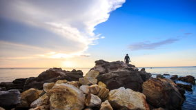 Backside Guy with Rods Walks on Stones to Sea at Sunset. Backside view guy with rods walks on large stones on beach to sea water for fishing against sky at stock footage