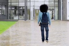 Afro student walks at school yard. Backside of a male Afro student walking on the school yard while holding books and carrying bag Stock Photo