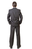 Backside of man in black suit keeping hands in pockets. Isolated on white background royalty free stock image