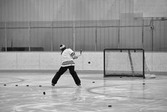 Backside of a man shooting pucks on a hockey net. The backside of a fourty year old man practicing shooting a bunch of pucks on an empty hockey net on a hockey Stock Photos