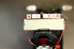 Backside of motorcycle. Backside of motorcycle plastic model carry small text cube spelling the word new year royalty free stock photography