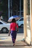 Backside of Myanmese woman walking on the walkway beside the street stock images