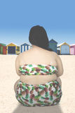 Backside of obese woman at coast. Backside of a young obese woman wearing swimwear and sitting on the beach Royalty Free Stock Photography