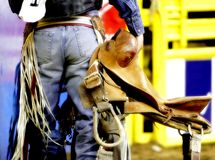 Backside of a Rodeo Cowboy with his Saddle. The backside of a Saddle Bronc cowboy with his saddle, before a rodeo competition (shallow focus, high color royalty free stock photography