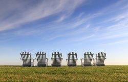 Backside of row of six white Adirondack chairs on lawn. Landscape includes backside of six white Adirondack chairs at the top of a sloping green lawn under a Stock Images