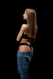 Backside of a sexy girl in blue jeans. Beauty girl in jeans from behind. Isolate on a black background Royalty Free Stock Photo
