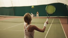 Backside slow motion footage of a female sportive tennis player hitting the ball with the racket at tennis court