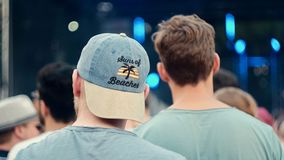 Two men in a festival crowd A. Backside of two man at a summer festival concert enjoying a live band Royalty Free Stock Photo