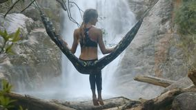 Girl Sits in Hammock Hanging on Tree by Waterfall. Backside view blond girl sits on hammock hanging on tree trunks against pictorial waterfall among rocks stock footage