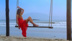 Girl Swings on Beach Rope Bench Looks at Blue Sea. Backside view blond long haired girl barefoot in red frock swings on beach rope bench looks at pictorial blue stock video footage