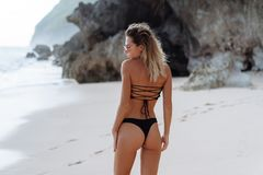 Backside view of girl with booty in black bikini resting on deserted beach. Beautiful model in swimwear walks along white sand on tropical island stock photography