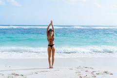 Backside view of girl with booty in black bikini resting on deserted beach. Beautiful model in swimwear walks along white sand on tropical island stock photos