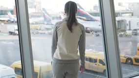 Backside view girl comes to window at airport and looks at aircraft, steadicam shot stock video footage