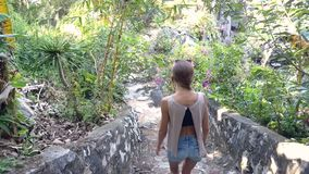 Backside view girl goes down stone steps between plants. Backside view girl in denim shorts goes down old stone steps between tropical plants on nice spring day stock video