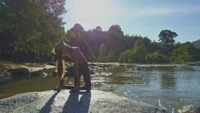 Backside View Girl with Ponytail Holds Pose on River Stone stock footage