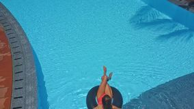 Girl with ponytail swims on ring in pool stock footage